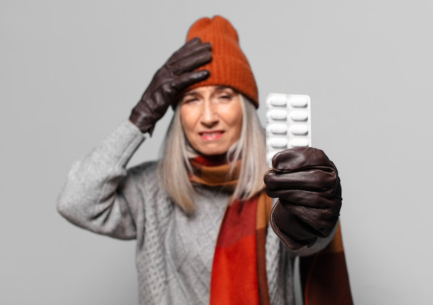 Senior ładna kobieta z tabletem pigułki na sobie ubrania zimowe. koncepcja grypy