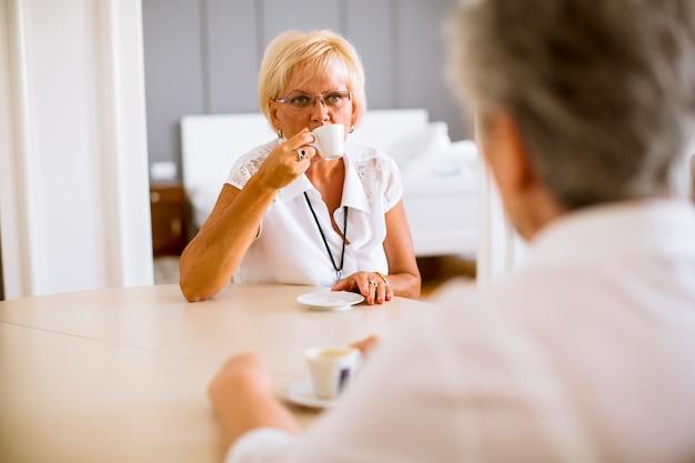 Senior matka i dojrzała stara córka opowiada kawę w pokoju i pije