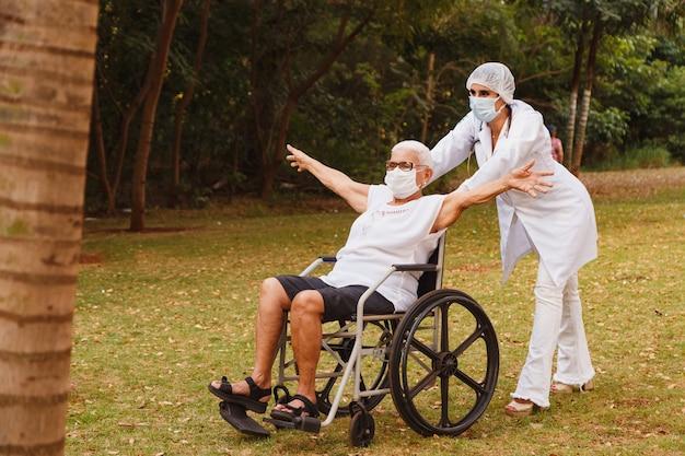Senior niepełnosprawna kobieta z opiekunem w ogrodzie domu opieki