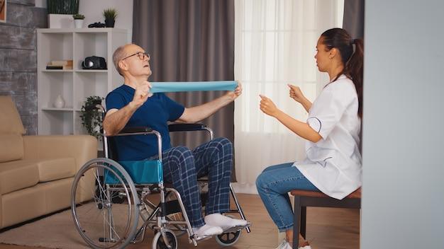 Senior niepełnosprawny pacjent na wózku inwalidzkim podczas rehabilitacji z terapeutą. osoba starsza niepełnosprawna niepełnosprawna z pracownikiem socjalnym w okresie rekonwalescencji terapia pomocnicza fizjoterapia służba zdrowia pielęgniarstwo emerytura