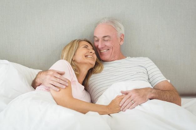Senior para obejmując na łóżku