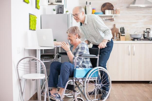 Senior para śmiejąc się podczas rozmowy wideo z wnukami przy użyciu komputera typu tablet w kuchni. sparaliżowana, niepełnosprawna starsza kobieta, korzystająca z nowoczesnych technologii komunikacyjnych.