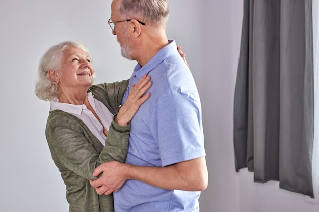 Senior para tańczy w salonie, mąż trzymający rękę dojrzałej żony ciesząc się wspólną zabawą, spędzać wakacje, emeryturę w czasie wolnym lub styl w domu. w codziennym stroju domowym