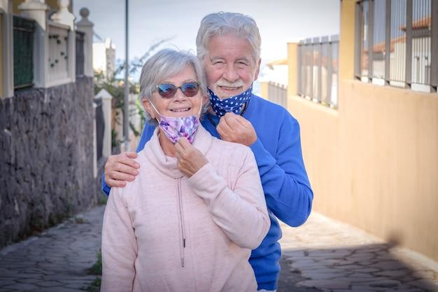 Senior para uśmiechający się na zewnątrz zdejmując maski ochronne przed zarażeniem koronawirusem. dwóch emerytów już zaszczepionych
