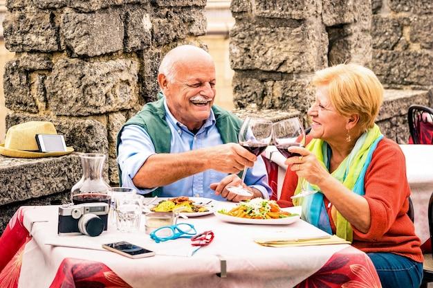 Senior para zabawy i jedzenia w restauracji - dojrzały mężczyzna i kobieta żona w barze starego miasta podczas aktywnych wakacji w podeszłym wieku - koncepcja szczęśliwej emerytury
