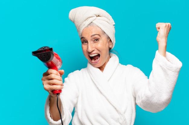 Senior pretty woman po prysznic na sobie szlafrok. koncepcja suszarki do włosów