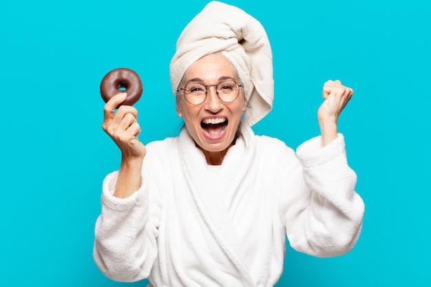 Senior pretty woman po prysznicem i na sobie szlafrok i śniadanie z pączkiem