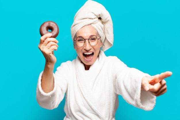 Senior pretty woman po prysznicem i nosząc szlafrok i jedząc śniadanie z pączkiem