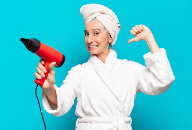 Senior Pretty Woman Po Prysznicem Na Sobie Szlafrok. Koncepcja Suszarki Do Włosów Premium Zdjęcia