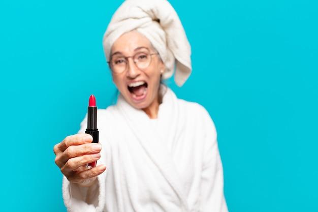 Senior pretty woman po prysznicem, uzupełniających i noszących szlafrok