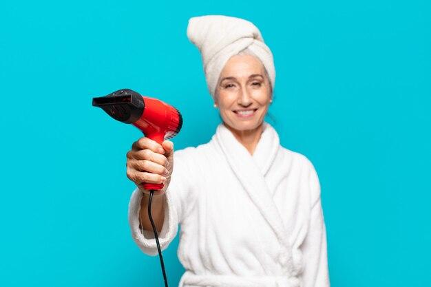 Senior pretty woman po prysznicu na sobie szlafrok i suszarkę do włosów