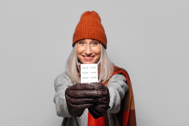 Senior pretty woman z tabletki pigułki na sobie zimowe ubrania. koncepcja grypy