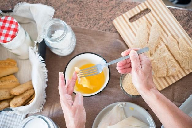 Senior sam w domu gotuje ryby w kuchni - bardzo skoncentrowany w pomieszczeniach - dojrzała i kaukaska kobieta z lat 60. - kobieta na emeryturze