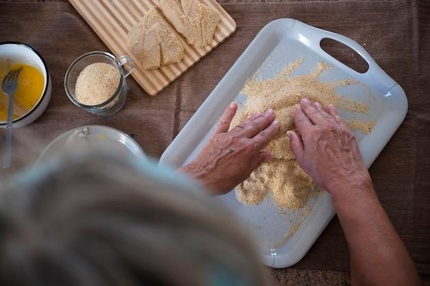 Senior sam w domu gotuje ryby w kuchni - bardzo skoncentrowany w pomieszczeniu - dojrzała i kaukaska kobieta z lat 60. - emerytowana kobieta - jej ręka jest na stole przygotowując rybę