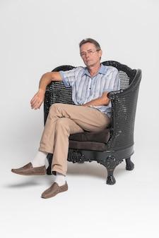 Senior siedzący w fotelu i zamyślony, rozmarzony