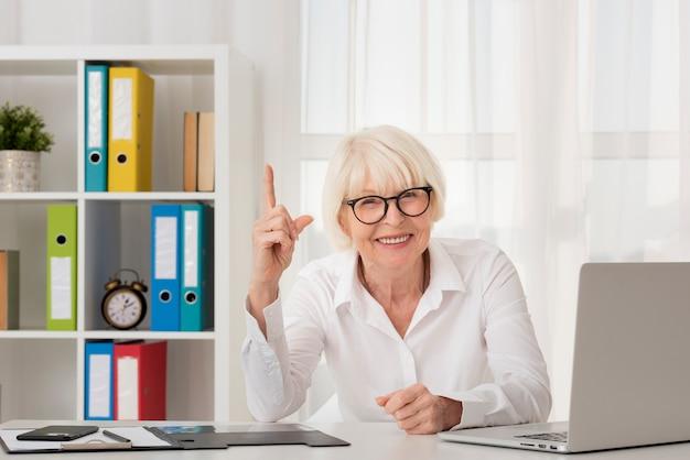 Senior siedzi w jej biurze z eyeglasses