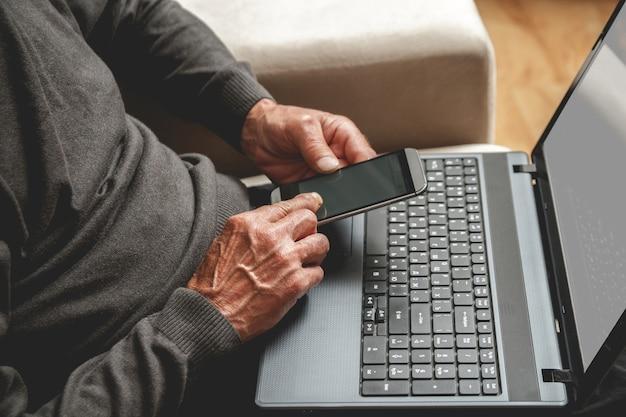 Senior siedział na kanapie z telefonem komórkowym w ręku i laptopem