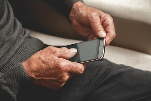 Senior siedział na kanapie z telefonem komórkowym w ręku