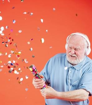 Senior słuchania muzyki i strzelanie konfetti