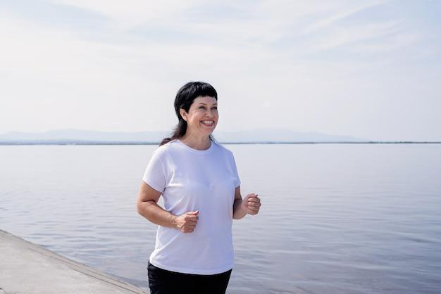 Senior sport. aktywni seniorzy. aktywny starszy kobieta jogging w pobliżu rzeki