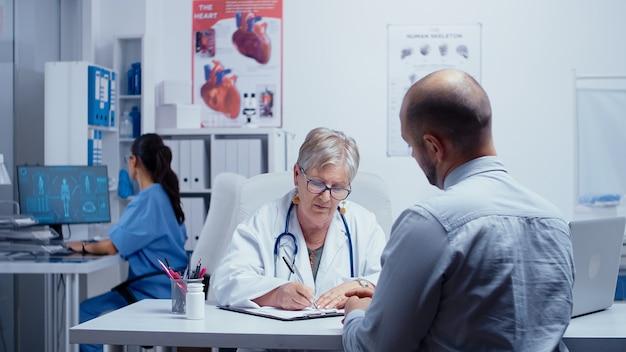 Senior starsza kobieta lekarz pisania recepty na młodego pacjenta płci męskiej w swoim gabinecie. opieka zdrowotna w nowoczesnym szpitalu lub przychodni prywatnej, profilaktyka chorób i konsultacje w gabinecie lekarskim