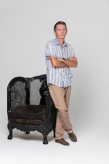Senior stoi przy fotelu i zamyślony, marzycielski z dala na białym tle
