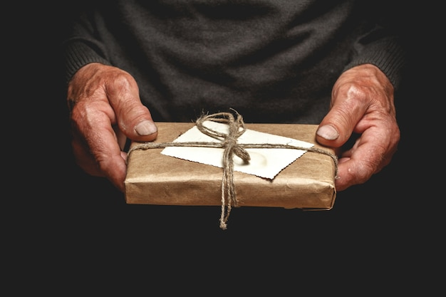 Senior trzyma prezent w opakowaniu vintage