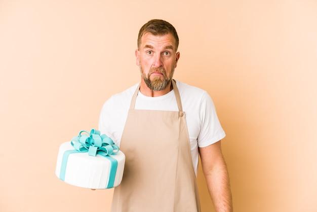 Senior trzymając tort na białym tle na beżowej ścianie wzrusza ramionami i zdziwiony otwartymi oczami.