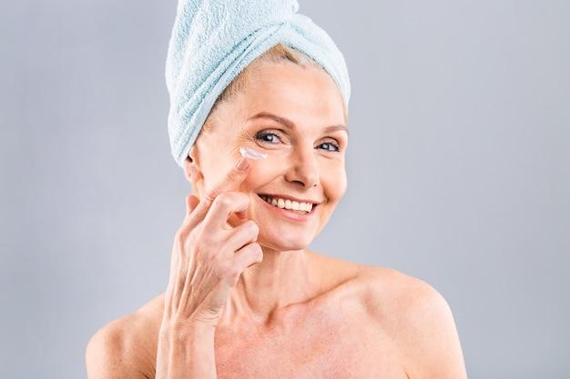 Senior uśmiechnięty 50s w średnim wieku dojrzała starsza kobieta nakłada krem do twarzy na twarz patrząc na aparat anty wiek zdrowy sucha skóra pielęgnacja terapia kosmetyczna koncepcja stara pielęgnacja skóry