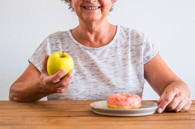 Senior wybierając między jabłkiem lub pączkiem - dieta i zdrowy styl życia - wybierz jej koncepcję stylu życia - trzyma jabłko i pączek na stole - uśmiechnięta kobieta
