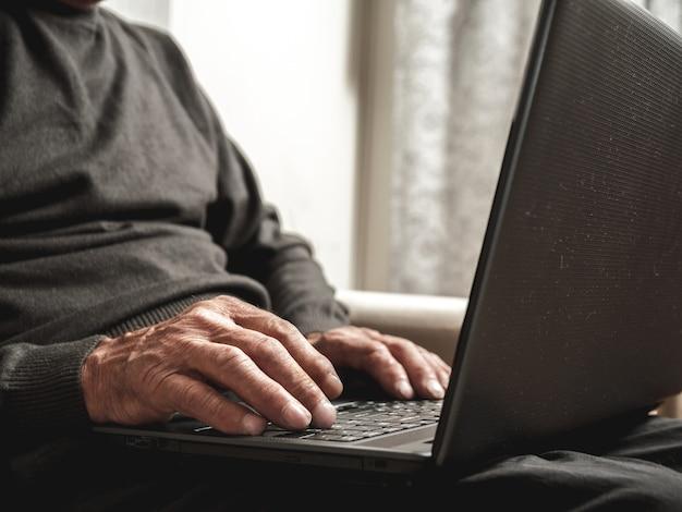 Senior z laptopem w rękach
