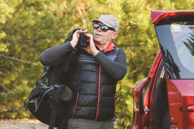 Senior z plecakiem w pobliżu suv-a w lesie