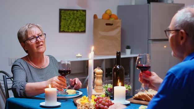 Senior zrelaksowany para razem je obiad i pije kieliszki czerwonego wina w kuchni w domu. osoby w podeszłym wieku, emeryci, delektujący się posiłkiem, świętujący swoją rocznicę w jadalni.