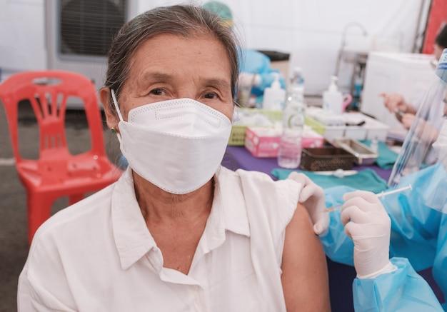 Seniorka z azji poszła na szczepienie koronawirusa covid z personelem medycznym w szpitalu polowym