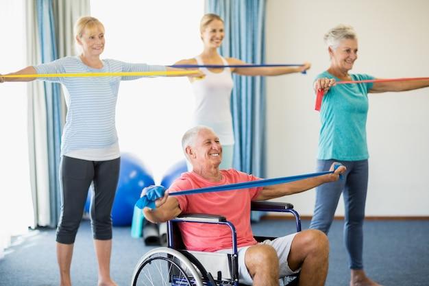 Seniorzy ćwiczący z zespołami rozciągającymi