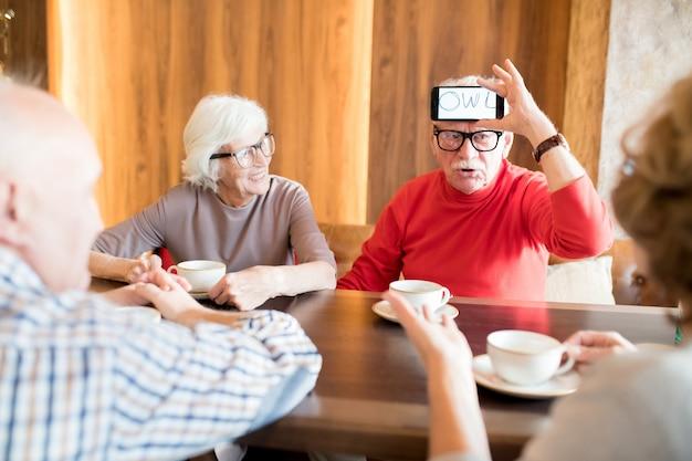 Seniorzy grający w zgadywanie słów w kawiarni