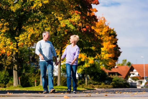 Seniorzy jesienią lub jesienią idą ramię w ramię