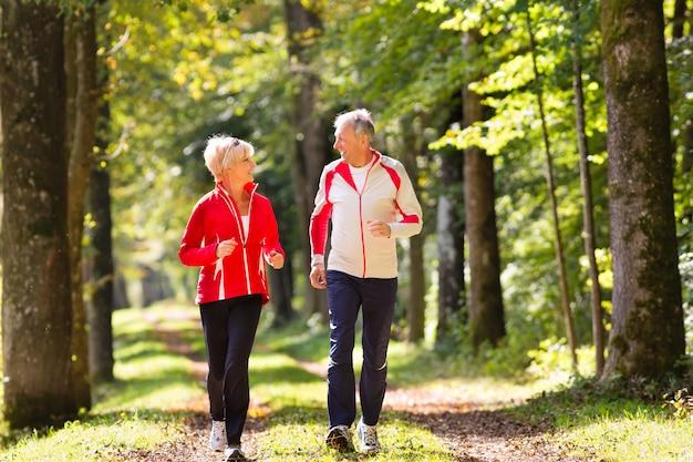 Seniorzy jogging na leśnej drodze
