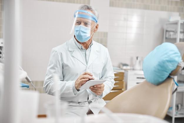 Seniorzy noszący fartuch laboratoryjny i maskę ochronną trzymający tablet podczas pracy w klinice dentystycznej
