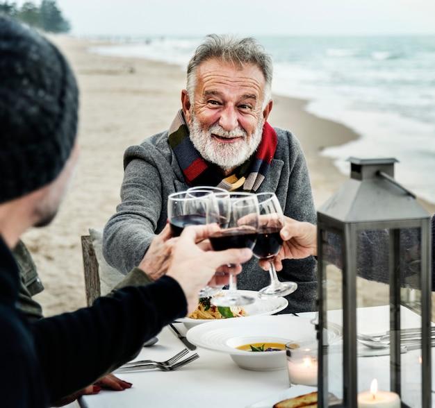 Seniorzy opiekania z czerwonym winem na plaży