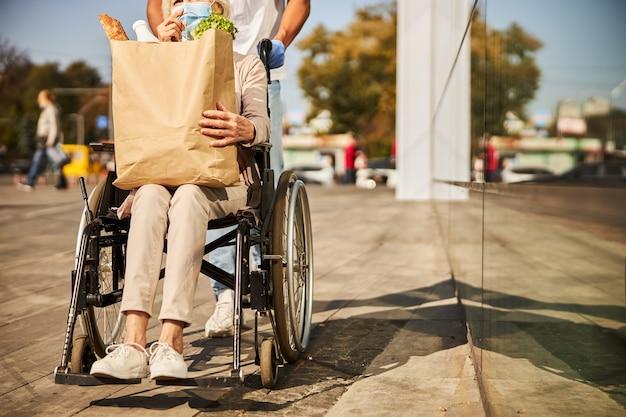 Seniorzy podróżujący na wózku inwalidzkim z domu towarowego z dużą papierową torbą na zakupy