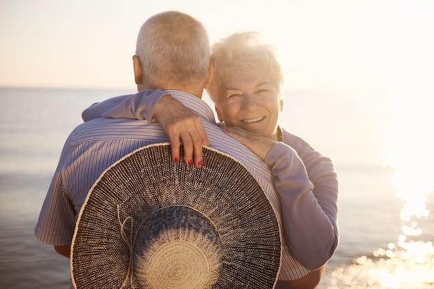 Seniorzy przytulający się nad morzem