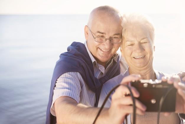 Seniorzy robią sobie selfie na plaży