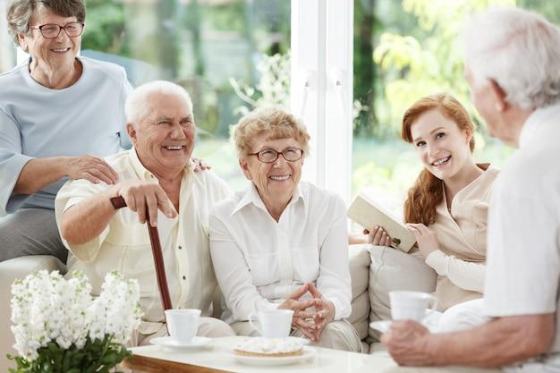 Seniorzy spędzają czas razem z młodym, rudowłosym opiekunem