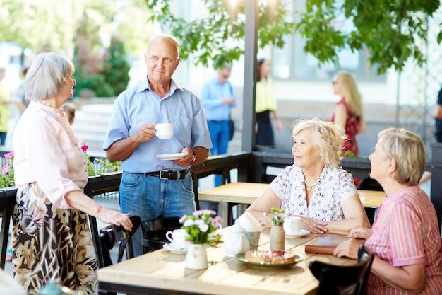 Seniorzy spędzający czas w kawiarni na świeżym powietrzu
