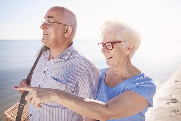 Seniorzy szukający dobrego miejsca na piknik na plaży