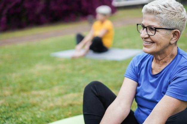 Seniorzy uczestniczący w zajęciach jogi utrzymujący dystans społeczny w parku miejskim
