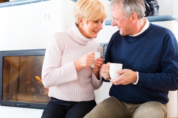 Seniorzy w domu przed kominkiem z filiżanką herbaty
