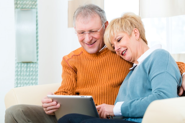 Seniorzy w domu z komputerem typu tablet