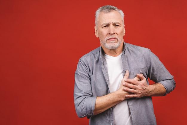 Seniorzy w wieku człowiek ma ból w klatce piersiowej na białym tle. pojęcie zdrowego stylu życia.